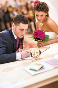 young_couple_signing_wedding_documents_focus_on_hand_